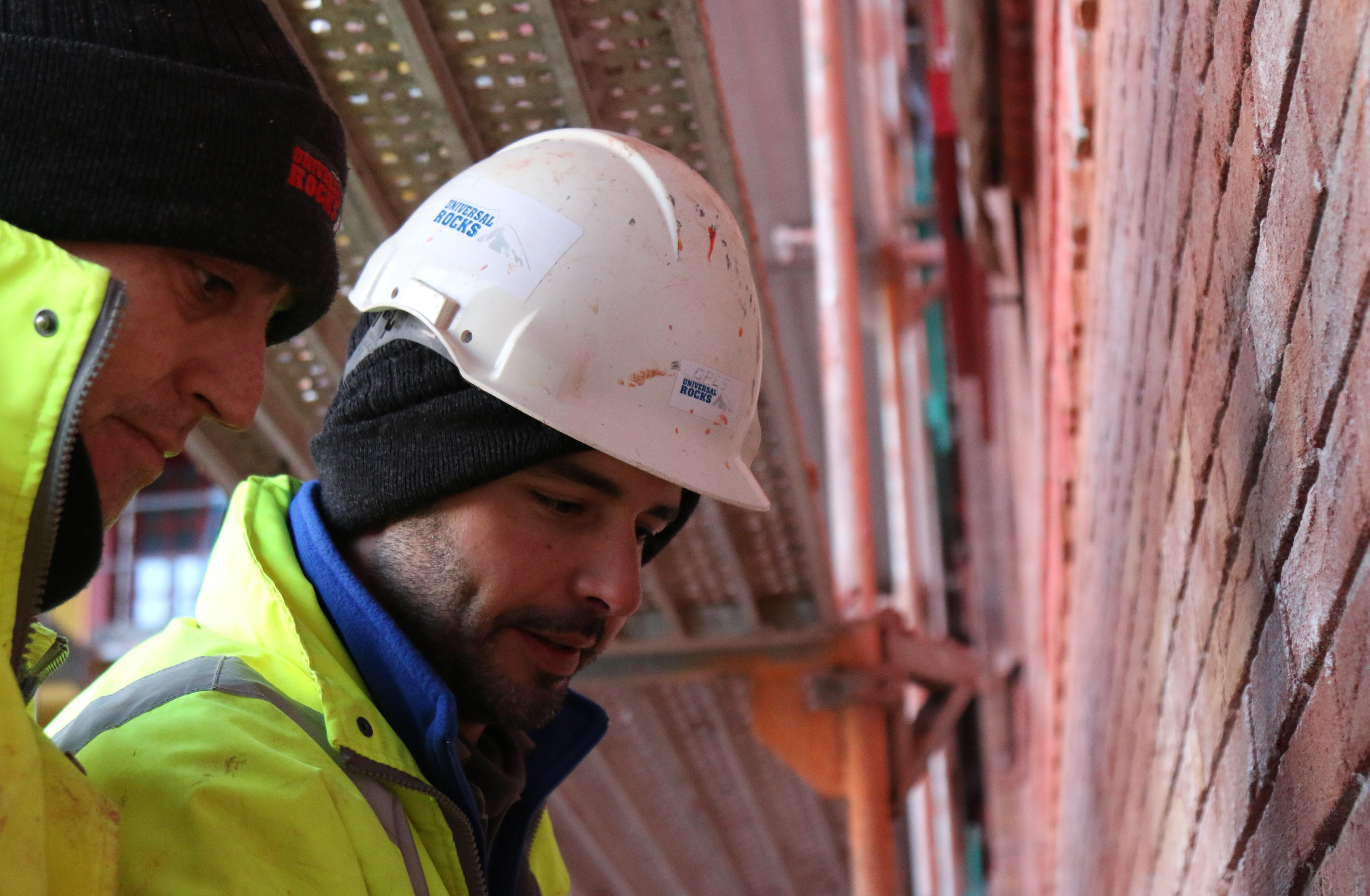 José Alberto Antunes Lopes (weißer Bauhelm) zeigt seinem Kollegen, was es noch zu tun gibt